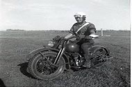 Photo of LCpl Otto Byko riding a military M/C in 1953.